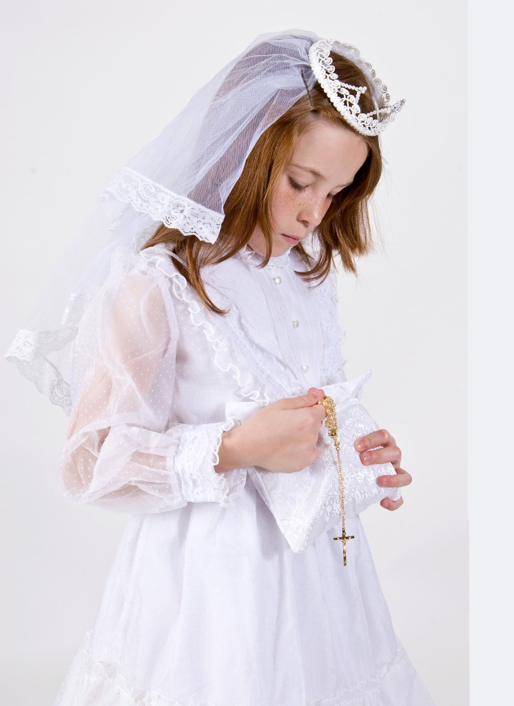 Young girl in First Communion Attire pulling rosary from purse